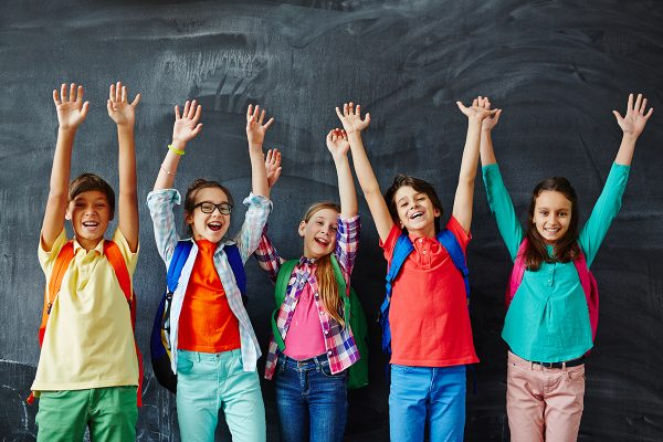 Ecstatic kids raising hands while standing by blackboard